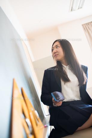 黒板の前で黒板消しを持っている女子高校生の素材 [FYI01078501]