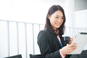 タブレットとコーヒーを持っている女性の素材 [FYI01078505]