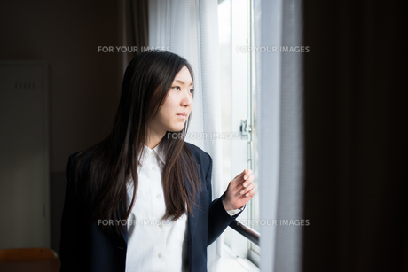 窓の外を眺めている女子高校生の素材 [FYI01078506]