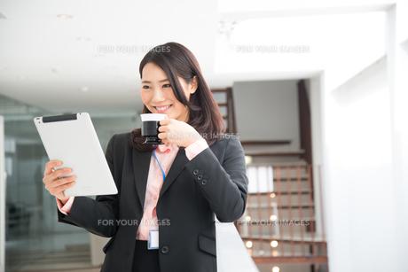 タブレットとコーヒーを持っている女性の素材 [FYI01078508]