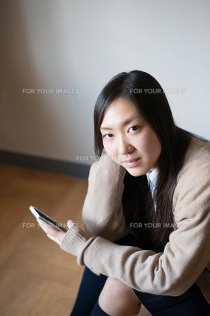 座って携帯電話を触っている女子高校生の素材 [FYI01078515]