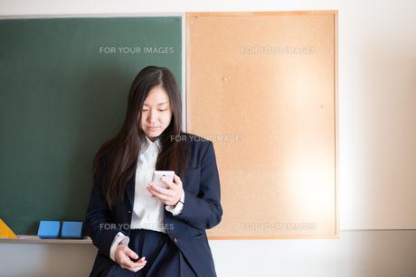 黒板の前で携帯をいじっている女子高校生の素材 [FYI01078517]
