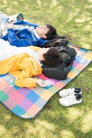 ピクニックマットの上に寝転がる男女の素材 [FYI01078518]