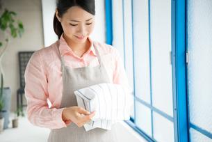 キッチンタオルを触っている女性の素材 [FYI01078519]