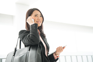 タブレットを持って電話をしている女性の素材 [FYI01078521]