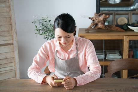 エプロン姿でスマートフォンを見ている女性の素材 [FYI01078523]