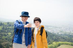 山頂で写真を撮っている男女の素材 [FYI01078524]