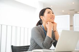ノートパソコンの前で頬杖をついている女性の素材 [FYI01078531]