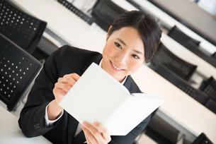 スケジュール帳を見ているスーツ姿の女性の素材 [FYI01078533]
