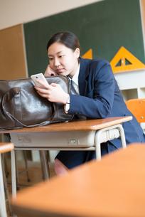 教室で携帯電話をいじっている女子高校生の素材 [FYI01078534]