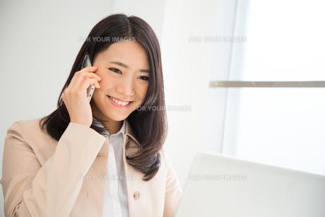 ノートパソコンを見ながら電話をしている女性の素材 [FYI01078536]