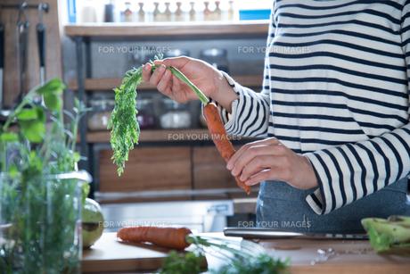 キッチンでにんじんを持っている女性の手元の素材 [FYI01078538]
