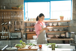 キチンでお皿を持っている女性の素材 [FYI01078539]