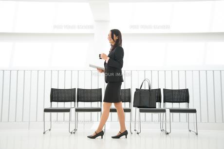タブレットとコーヒーを持って歩いている女性の素材 [FYI01078542]