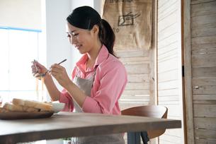 エプロンをしてパスタを食べようとしている女性の素材 [FYI01078544]