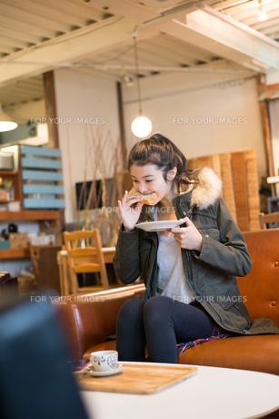 カフェでサンドイッチを食べている女性の素材 [FYI01078549]