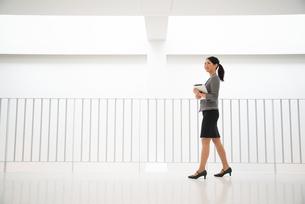 タブレットを抱えて歩いている女性の素材 [FYI01078559]