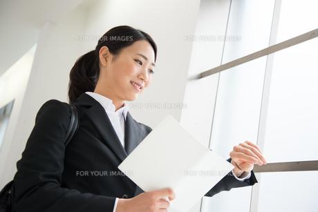 スケジュール帳を持って時計を見ているスーツ姿の女性の素材 [FYI01078561]