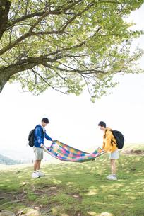山頂でピクニックマットを広げている男女の素材 [FYI01078566]