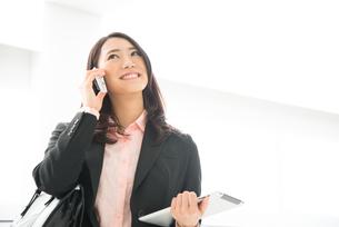 タブレットを持って電話をしている女性の素材 [FYI01078567]