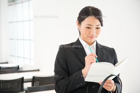 スケジュール帳を見ているスーツ姿の女性の素材 [FYI01078575]