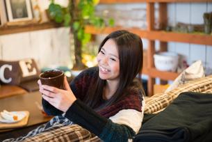 カフェでカップを持っている女性の素材 [FYI01078576]