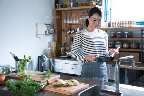 キッチンでフライパンを持っている女性の素材 [FYI01078577]