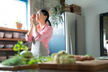 キッチンでりんごを食べようとしている女性の素材 [FYI01078582]