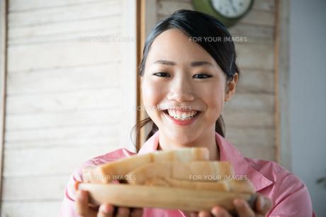 食パンを持って笑っている女性の素材 [FYI01078590]