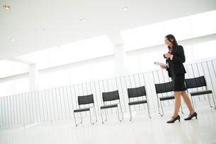 タブレットとコーヒーを持って歩いている女性の素材 [FYI01078602]