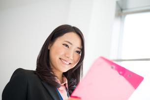 ファイルを見て笑っている女性の素材 [FYI01078613]