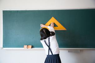 黒板にチョークで線を書く小学生の女の子の素材 [FYI01078617]
