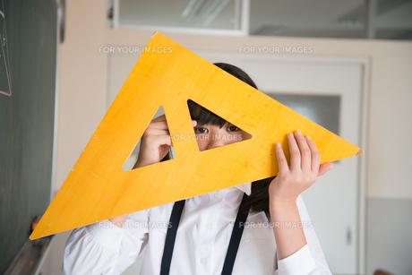 黒板の前で三角定規を持っている小学生の女の子の素材 [FYI01078621]