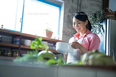 キッチンで白い鍋を持って笑っている女性の素材 [FYI01078624]