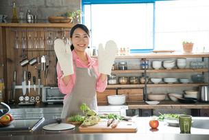 鍋つかみをして笑っている女性の素材 [FYI01078633]