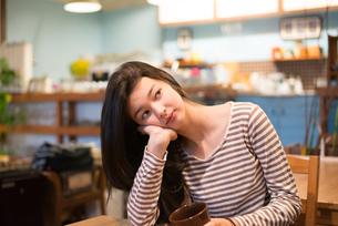 カフェで頬杖をついている女性の素材 [FYI01078635]