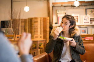 カフェでサンドイッチを食べている女性の素材 [FYI01078636]