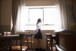 教室の窓の外を見ている小学生の女の子の素材 [FYI01078639]