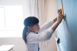 黒板にチョークで線を書く小学生の女の子の素材 [FYI01078644]