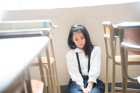 教室の床に座っている小学生の女の子の素材 [FYI01078648]