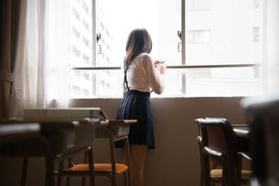 教室の窓の外を見ている小学生の女の子の素材 [FYI01078649]