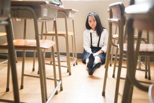 教室の床に座っている小学生の女の子の素材 [FYI01078674]