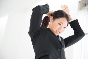 髪を結んでいるスーツ姿の女性の素材 [FYI01078682]