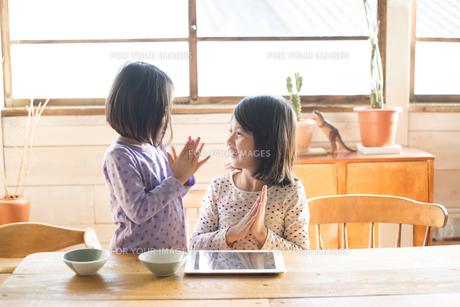 タブレットを前に喜んでいる姉妹の素材 [FYI01078688]
