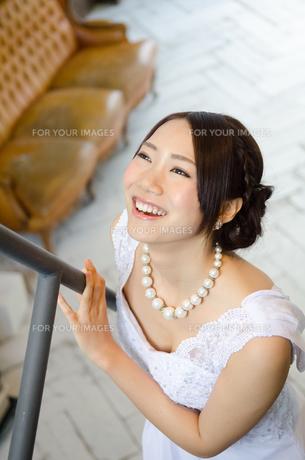 手すりを触りながら笑うドレス姿の女性の素材 [FYI01078691]