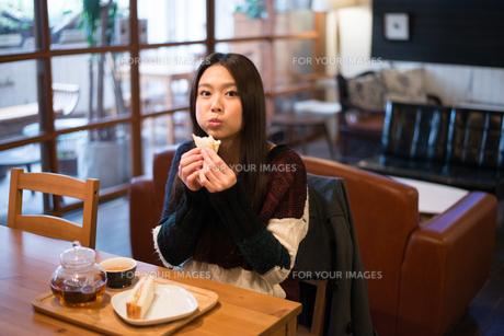 カフェでサンドイッチを食べている女性の素材 [FYI01078692]