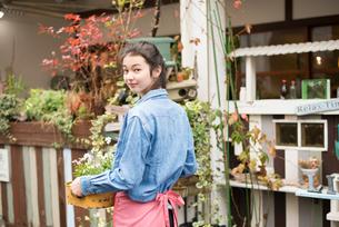 お花を持って振り返っている女性の素材 [FYI01078694]