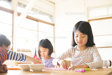 テーブルで遊んでいる子供たちの素材 [FYI01078699]