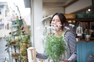 お花の鉢を持って笑っている女性の素材 [FYI01078710]