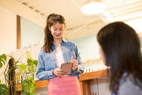 カフェで注文を取っている女性の素材 [FYI01078719]